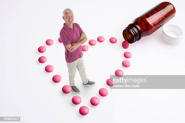 Senior man stands amongst heart-shaped pills