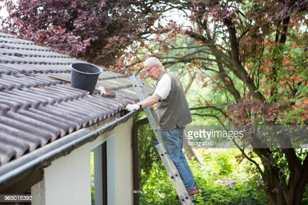senior man stands on ladder and cleans a roof gutter
