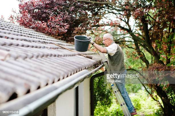 senior man stands on ladder and cleans a roof gutter - ladder stock pictures, royalty-free photos & images