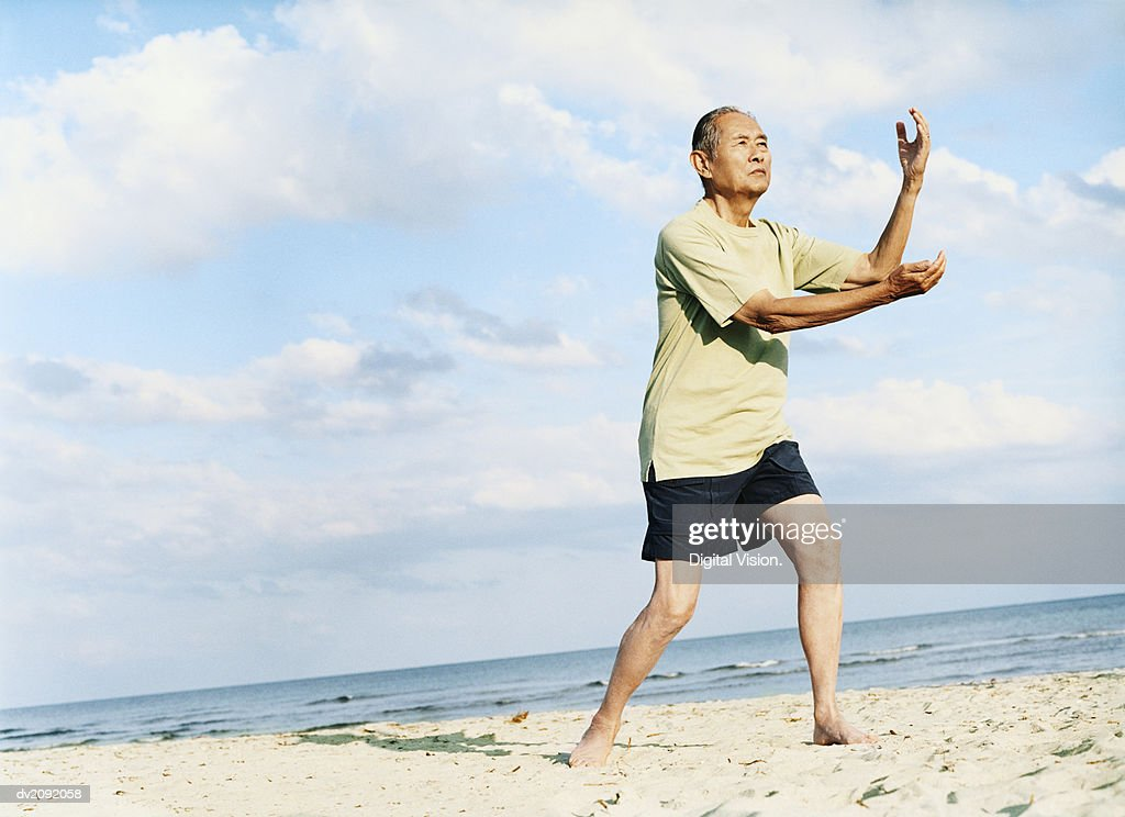 Senior Man Stands on the Beach Doing Tai Chi : Stock Photo