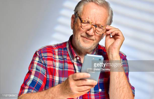 senior man staring at his smart phone in confusion - suspicion stock pictures, royalty-free photos & images