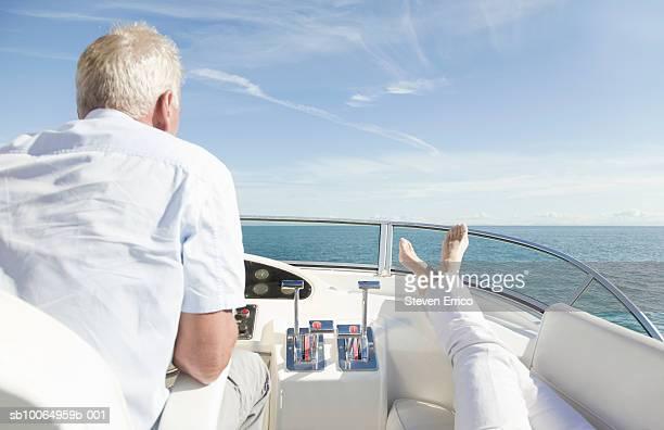 Senior man steering yacht, woman's feet resting on console