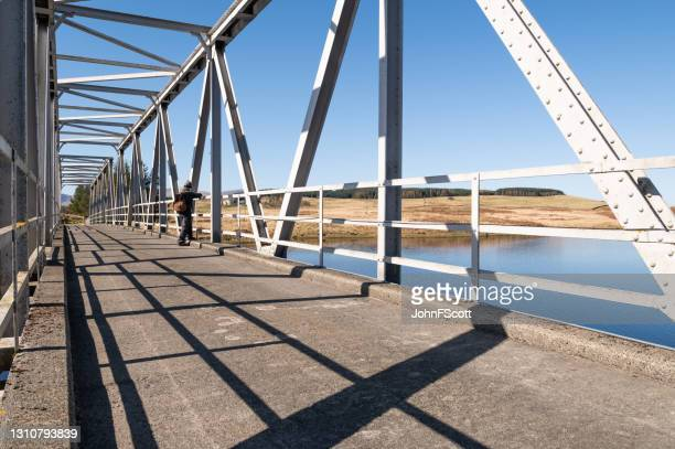 senior man stopping to look from a steel bridge - johnfscott stock pictures, royalty-free photos & images