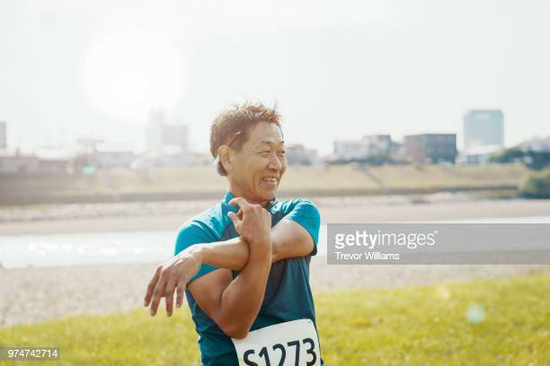 senior man stretching after running a marathon - japanese old man stock pictures, royalty-free photos & images