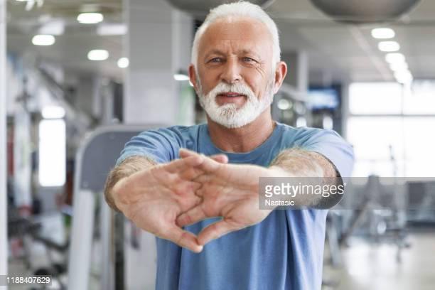 senior mann streckt arme in fitness-studio - menschliche gliedmaßen stock-fotos und bilder