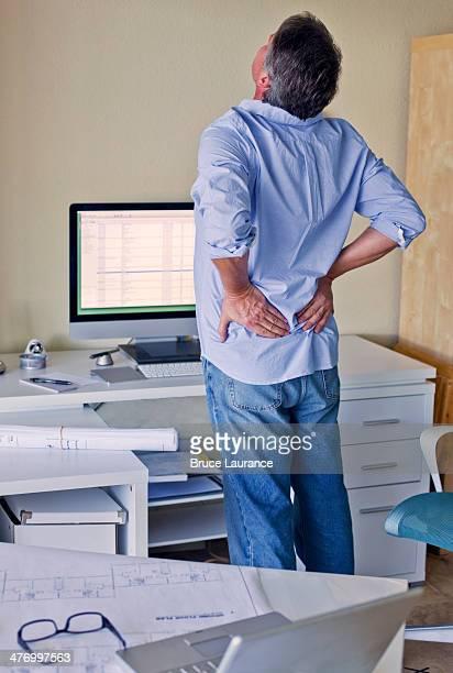 Senior man stretching at desk