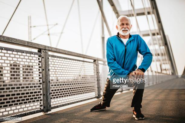 senior man stretching before running - white hair stock pictures, royalty-free photos & images