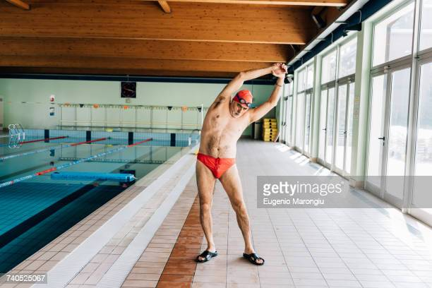 senior man stretching by swimming pool - zwembroek stockfoto's en -beelden
