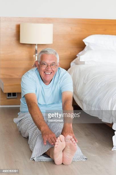 Senior man stretching legs in bedroom