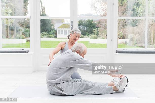Senior man stretching legs with female fitness instructor watching