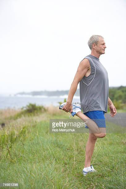 senior man stretching, side view - standing on one leg stock pictures, royalty-free photos & images
