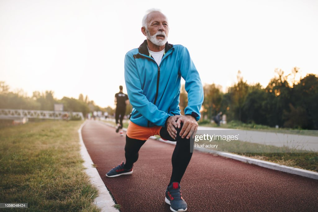 Senior man stretching while jogging on a running track : Stock Photo