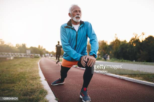 senior man stretching while jogging on a running track - young at heart stock pictures, royalty-free photos & images