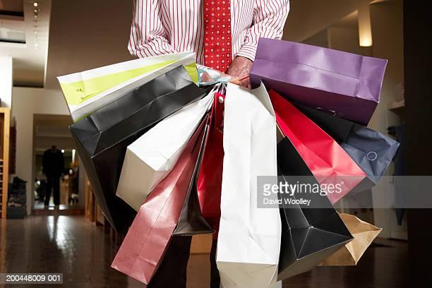 senior man struggling with multiple shopping bags, mid section - viele gegenstände stock-fotos und bilder