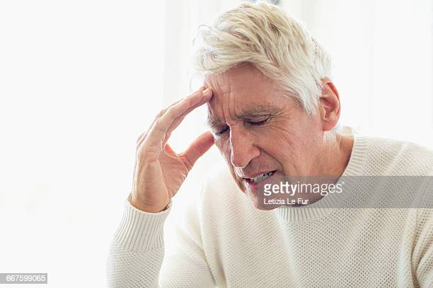 senior man suffering from headache - grimassen stockfoto's en -beelden