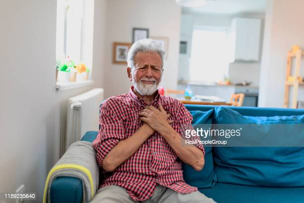 senior man suffering from heart attack at home - heartburn stock photos and pictures