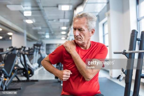 senior man suffering from shoulder pain at rehabilitation center - pain stock pictures, royalty-free photos & images