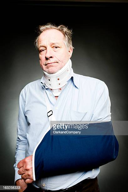 Senior Man Suffering From Whiplash With Sling and Neck Brace