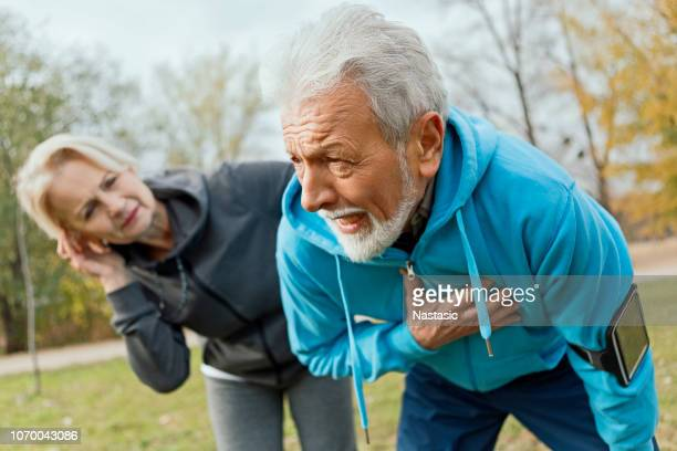 senior man suffering heart attack whilst jogging - heart attack stock pictures, royalty-free photos & images