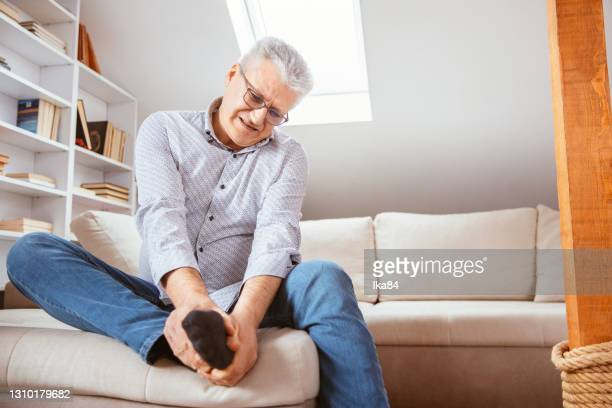 senior man suffering with foot cramp - human foot stock pictures, royalty-free photos & images
