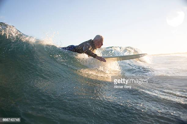 senior man surfing - paddling stock pictures, royalty-free photos & images