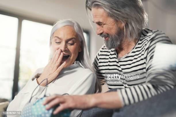 senior man surprising wife with a gift - gift lounge stock-fotos und bilder