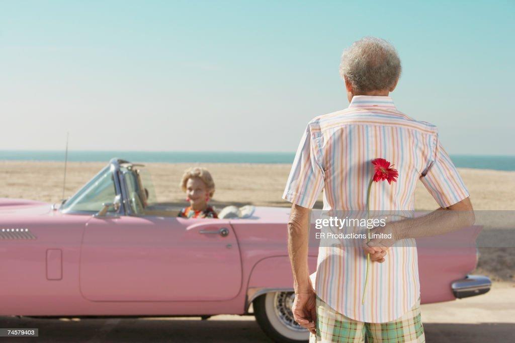 Senior man surprising wife with flower : Stock Photo