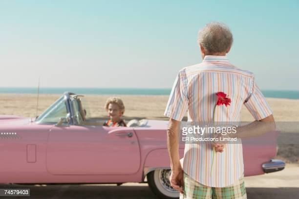 senior man surprising wife with flower - anniversary stock pictures, royalty-free photos & images