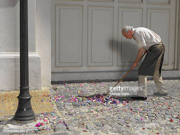 Senior man sweeping up coloured confetti in street