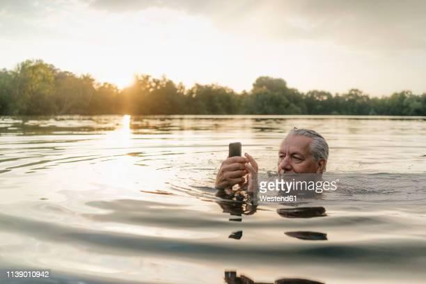 senior man swimming in a lake at sunset using cell phone - bizarr stock-fotos und bilder