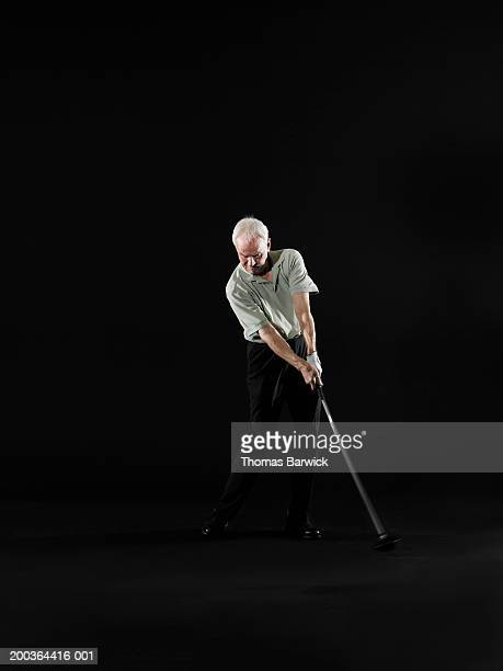 Senior man swinging golf club (blurred motion)