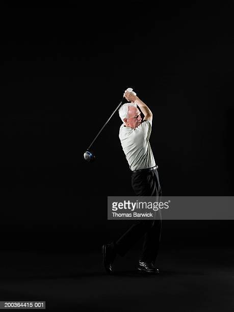 senior man swinging golf club, side view - essayer de marquer photos et images de collection