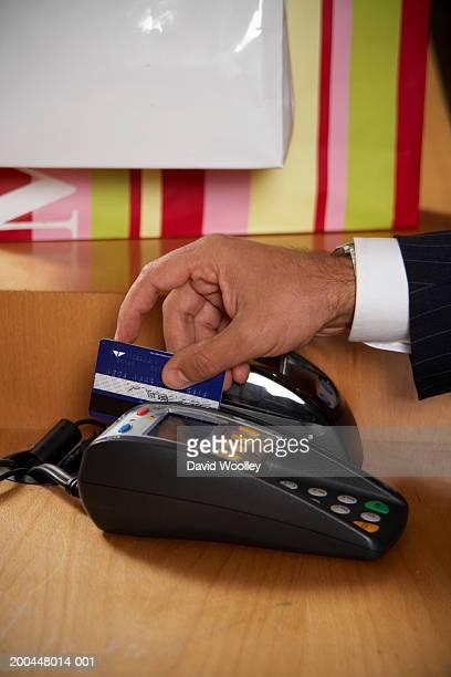 Senior man swiping credit card through pin code machine, close-up