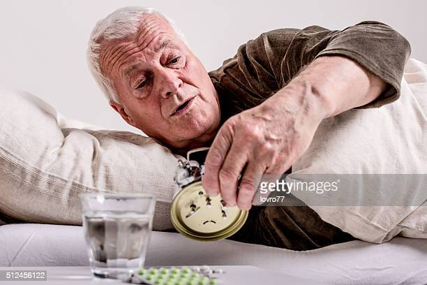 Senior man switching off the alarm clock