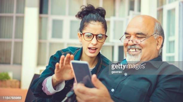 senior man takes help in smartphone from a young woman. - south asia stock pictures, royalty-free photos & images