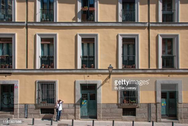 senior man taking a photograph in madrid old town - fachada arquitectónica fotografías e imágenes de stock