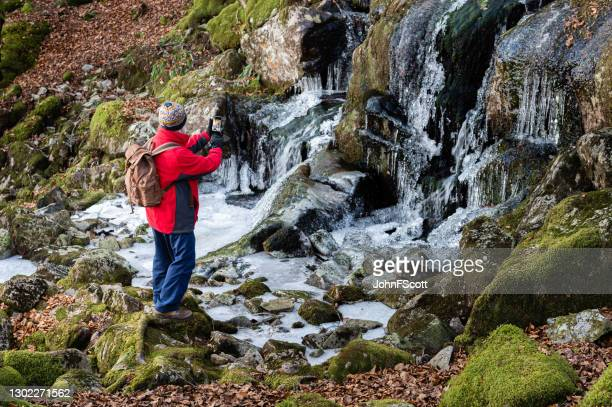 senior man taking a photograph of a frozen waterfall - johnfscott stock pictures, royalty-free photos & images