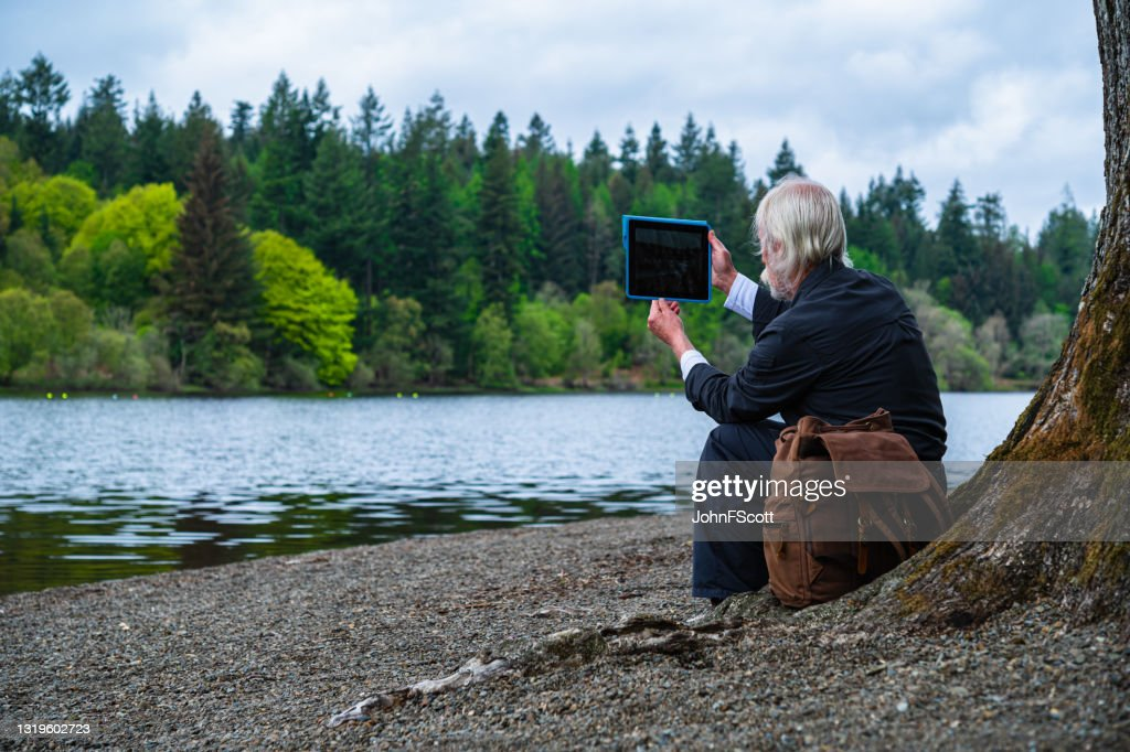 Senior man taking a photograph with a digital tablet : Stock Photo