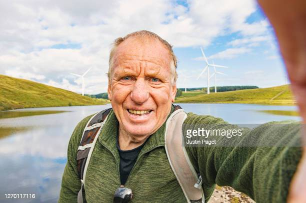 senior man taking a selfie whilst out hiking - reservoir stock pictures, royalty-free photos & images