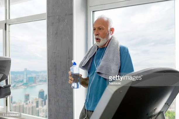 homem sênior que toma a ruptura dentro do funcionamento da escada rolante - 65 69 anos - fotografias e filmes do acervo