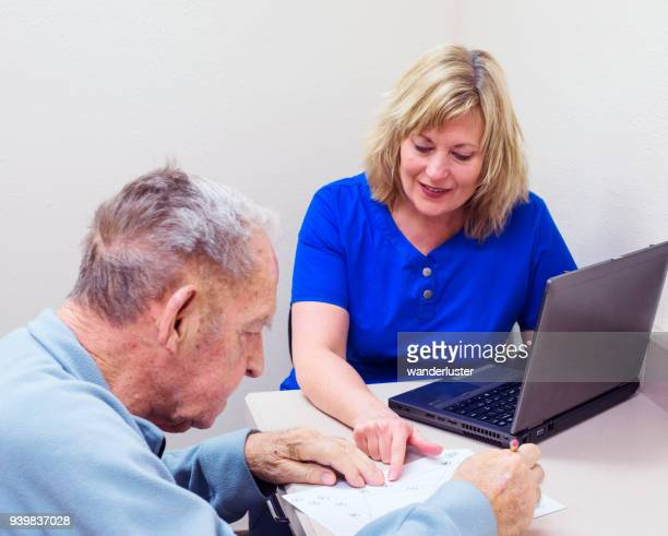 Senior man taking cognitive test in speech therapy session