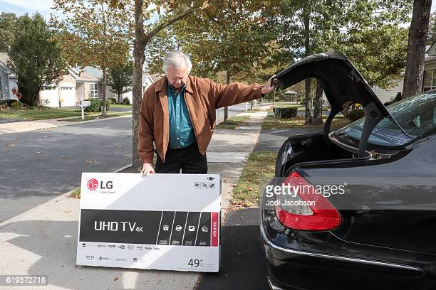 Senior man taking new television out of car trunk