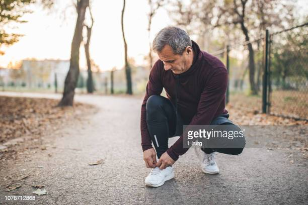 senior man taking pause from jogging to tie his shoelace - tying shoelace stock pictures, royalty-free photos & images