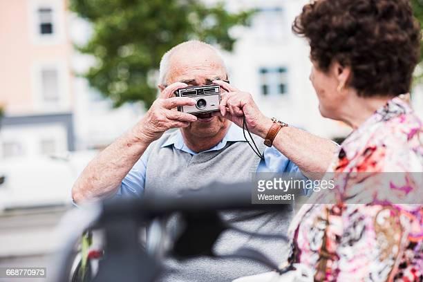 Senior man taking photo of his wife