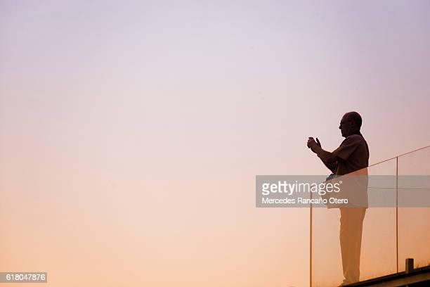 Senior man taking photographs, glass railing, sunset  background.