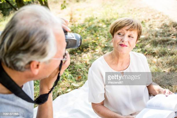 Senior man taking picture of his wife in meadow