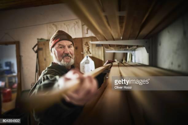 senior man taking piece of wood from shelf - handwerker stock-fotos und bilder