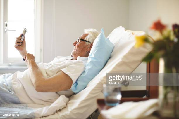 Senior man taking selfie with smart phone on bed in hospital ward