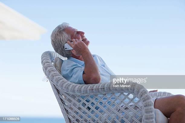 Senior man talking cell phone on beach patio