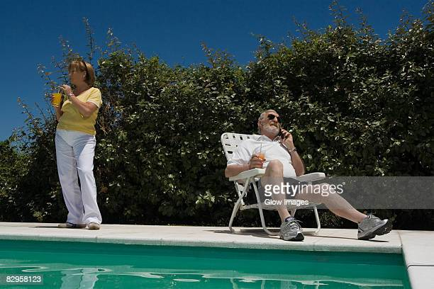 senior man talking on a mobile phone and senior woman drinking juice at poolside - woman sitting on man's lap stock pictures, royalty-free photos & images